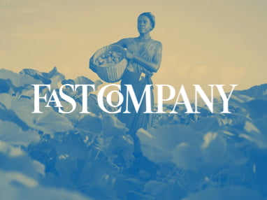 Fast Company logo superimposed over a woman carrying a basket of harvested goods.