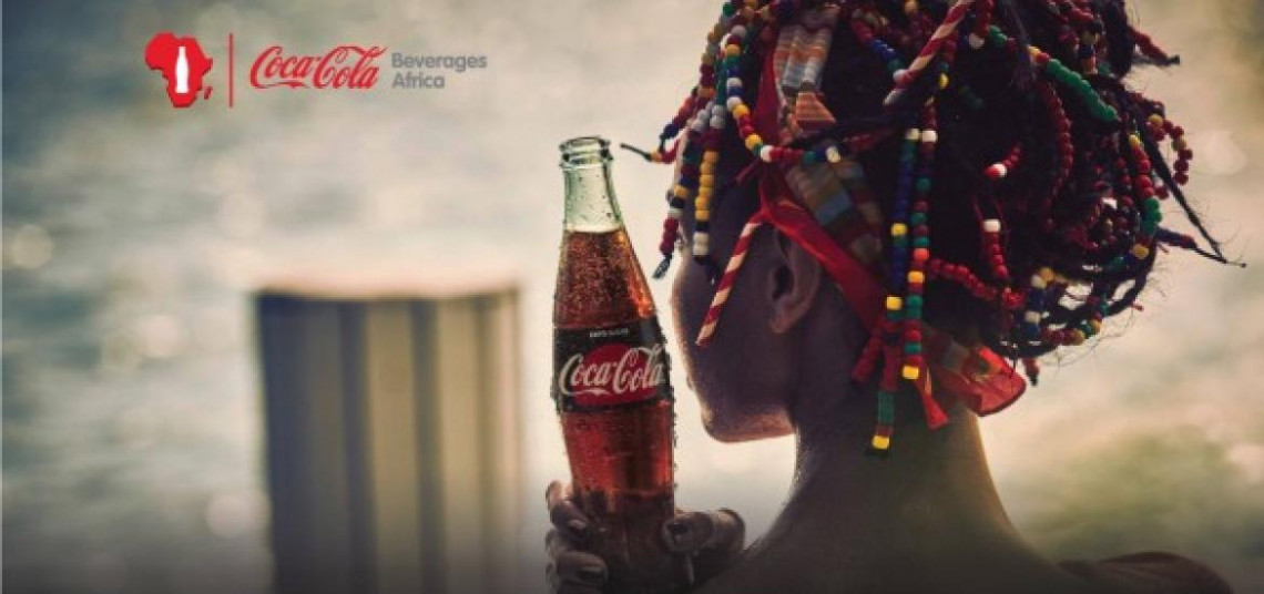 Woman holding a Coca-Cola outside with Africa logo overlay