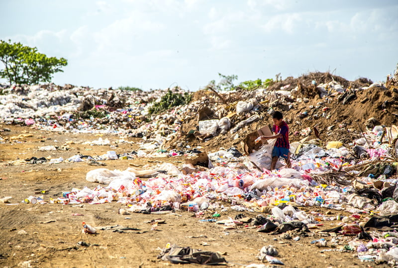 Child collecting recyclables from massive pile of garbage